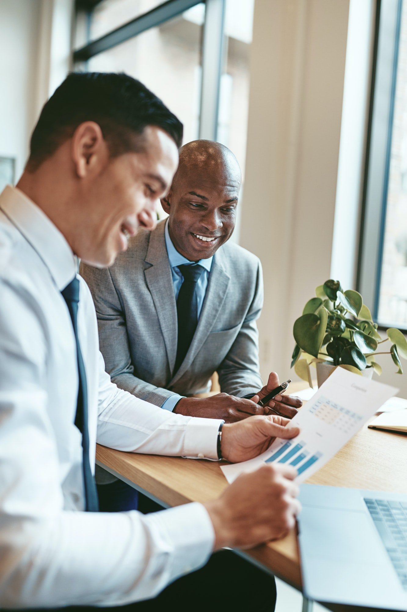 Two diverse businessmen smiling while reading paperwork in an office